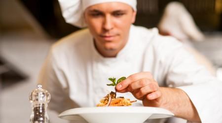 Chef dressed in white uniform decorating pasta salad