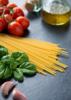 Fresh ingredients to make pasta with tomato sauce on blackboard